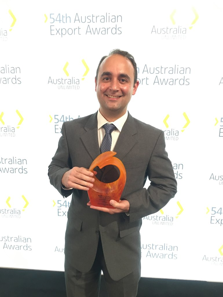 A man in a suit holds an award